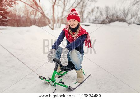 Happy young woman riding snowmobiles on winter snow hill.