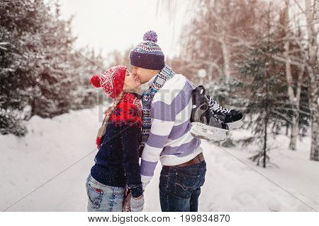 Loving Couple Kissing On A Date In A Winter Park. On The Back Of A Guy Hangs A Pair Of Skates.