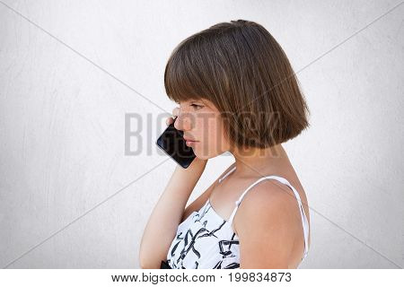 Sideways Portrait Of Little Girl With Bobbed Hair, Wearing White Dress, Speaking Over Cell Phone Wit