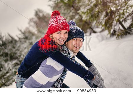 Winter, Fashion, Couple Concept - Smiling Man And Woman In Hats And Scarf Hugging Over Forest Backgr
