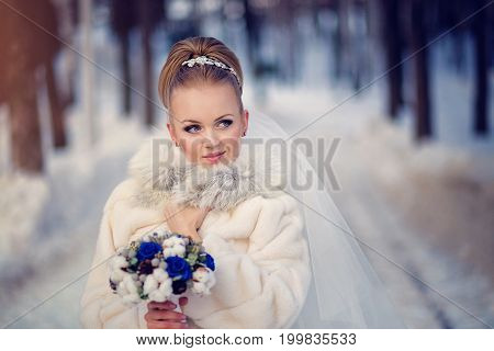 The bride in a fur coat with a bouquet and a veil in winter snowy forest.