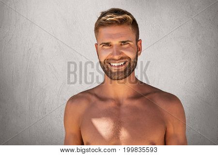 Glad Bodybuilder With Biceps Posing Topless With Pleasant Smile, Being Happy To Spend Free Time In G