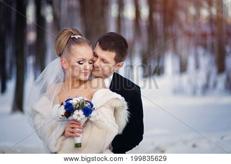 Wedding Bride And Groom Kissing And Loving Tender Couple With  Bouquet Of Blue Flowers At Winter Bri