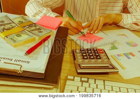 Business plan calculator dollar banknote on the table. Savings finances economy Business and home concept - Female with calculator counting money and making notes at home - Retro color