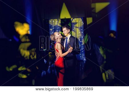 Stylish Luxury Bride In Red Dress And Groom Dancing In A Restaurant, Celebrating Wedding