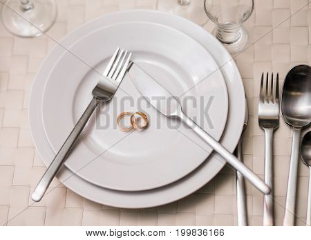 Two Rings On A Plate With Serving Fork, Spoon, Knife. The Concept Of A Wedding Celebration At Banque