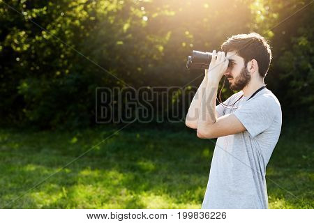 Young Bearded Male Looking Through Binoculars While Standing At Green Field, Observing Something. Ha