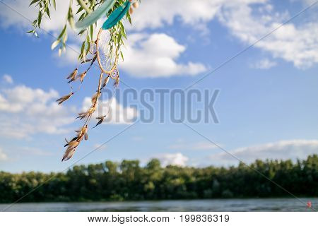 The Dreamcatcher Hangs On A Tree On Blue Sky Background With Copy Space