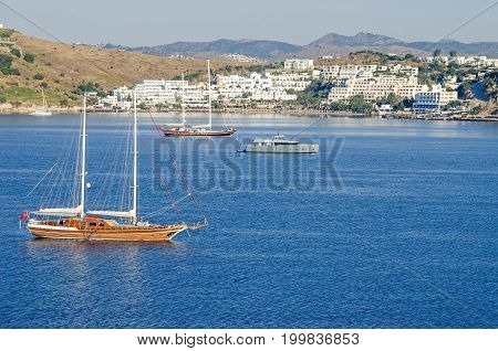 Bodrum Turkey - June 1 2017: View of the white city of Bodrum from the sea with the Gulet type schooners (a two-masted wooden sailing vessel) popular for tourist charters and motorboats.