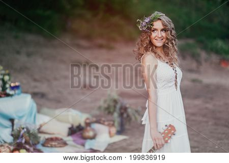 Girl At A Summer Picnic In A Sundress And A Wreath Of Wild Flowers With Copy Space