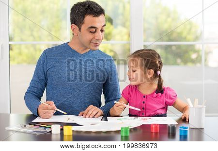 Little Girl And Father Are Painting Pictures Together
