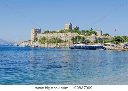 Bodrum Turkey - June 1 2017: View of the Bodrum Castle or St. Peter's Castle from the south-east built in 15th century by the Knights Hospitaller out of squared green volcanic stone with a ferryboat in front.