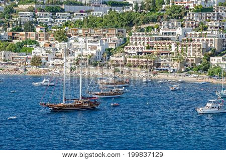 Bodrum Turkey - June 1 2017: View of the white city of Bodrum from the sea with the Gulet type schooners (a two-masted wooden sailing vessel) popular for tourist charters and a city beach empty of people.