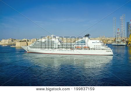 Senglea Malta - June 4 2017: Cruise liner Seabourn Odyssey with Senglea peninsula in a background as seen from Valletta.