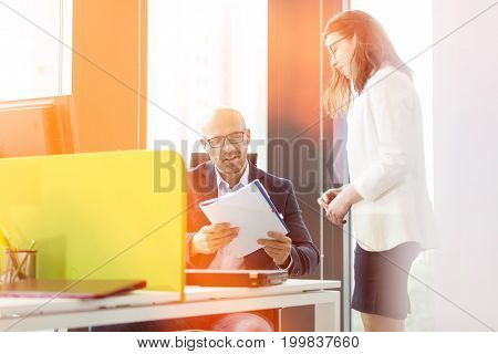 Young businesswoman standing by businessman reading book at office