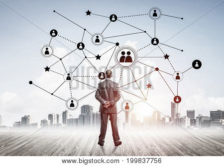 Back view of businessman looking at modern cityscape and connection concept