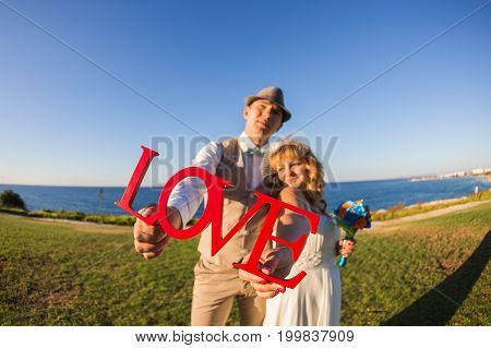 Bride and groom holding the letter word love near sea