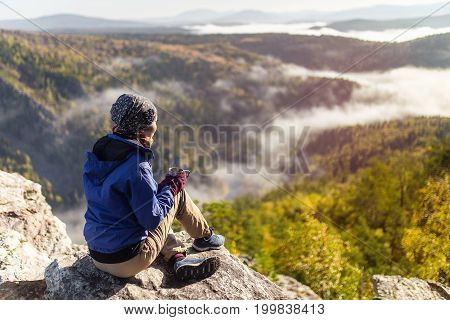 Tourist Young Woman Is Sitting With A Mug Of Tea On A Cliff Overlooking The Autumn Mountains With Fo