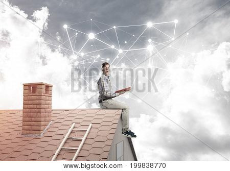 Young student man sitting on house with red book in hands