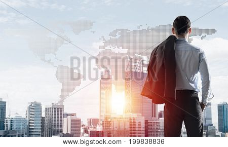 Young elegant businessman with jacket on shoulder looking away