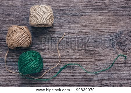 Green and beige tangles of thread on a wooden surface. Linen yarn