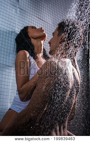Young nude man and woman in white shirt making love in shower