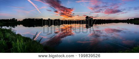 The Reflection Of The Sunset Sky In Lake Water. Wide Panoramic Shot