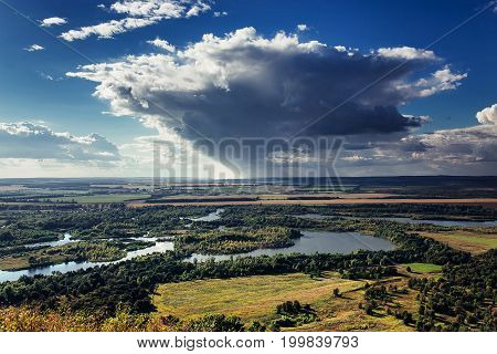 Beautiful Landscape, Green And Yellow Meadow And Lake With Strom Rain Clouds In The Background