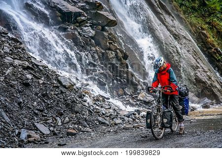 Female passing one of many waterfalls while cycling through the Tiger Leaping gorge, Yunnan Province, China