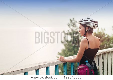 Young tourist woman with helmet standing at the railing of the bridge on the road