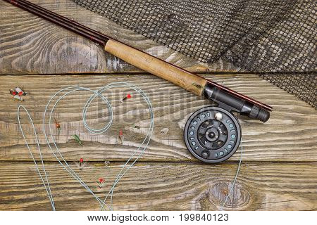 Fly fishing rod , box of flies and a landing net on the old wooden table. All ready for fishing.