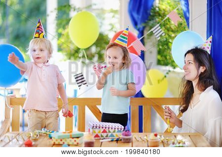 Cute little boy and girl having fun and celebrate birthday party with colorful decoration and cakes