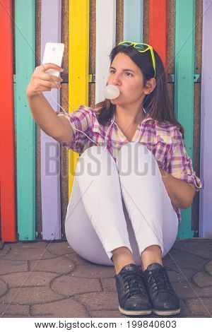Young beautiful female sitting making bubble gum balloon and taking selfie in front of multicolored wooden wall. Technology and youth culture concepts.