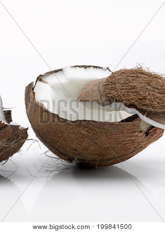 One Whole Coconut Broken into Two Pieces with One Piece on Left Side