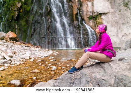 woman traveler in bright clothes resting by the Gegsky waterfall in Caucasus Abkhazia