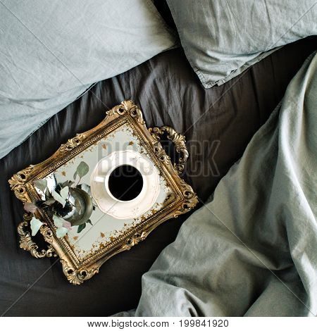 Morning coffee on golden vintage tray in bed with grey sheet and pillows. Flat lay top view.