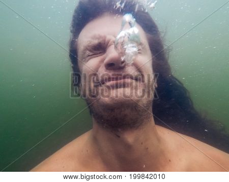 Young man sinks in water or drowns, air bubbles, face grimace, underwater photo, selective focus