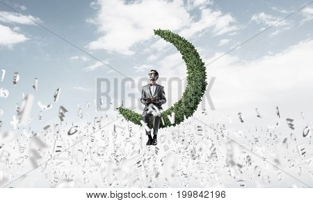 Funny man in red glasses and suit sitting on green moon and reading book