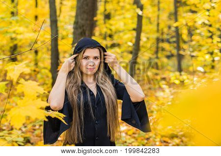 Portrait of beautiful girl as witch dressed in a dress with a hood. Halloween, masquerade, holidays, autumn and people concept.