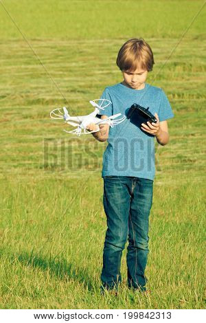 Little boy playing with drone in summer day outdoors.