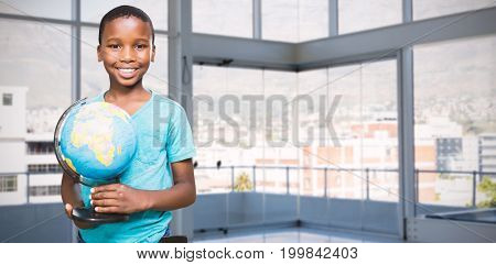 Portrait of smiling boy holding globe against buildings seen through office