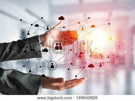 Business woman in suit keeping black social media network structure in hands with sunlight and office view on background. Mixed media.