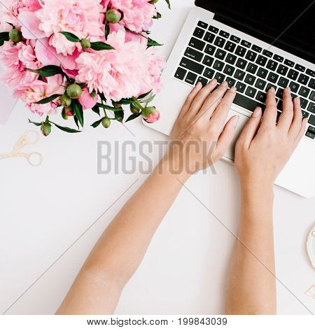 Flat lay home office desk. Workspace with girl's hands laptop pink peony bouquet golden accessories. Top view