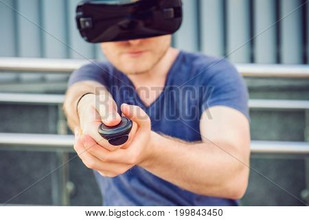 Young Man Pressing The Control Panel Button Enjoying Virtual Reality Glasses Or 3D Spectacles On The