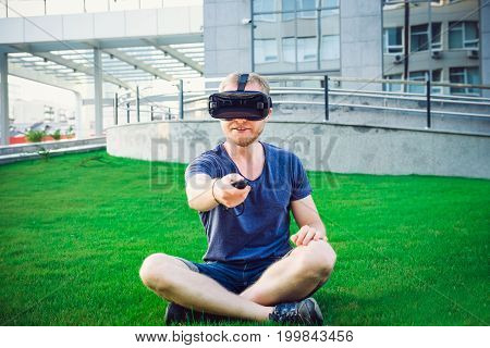Young Man Pressing The Control Panel Button Enjoying Virtual Reality Glasses Or 3D Spectacles In The