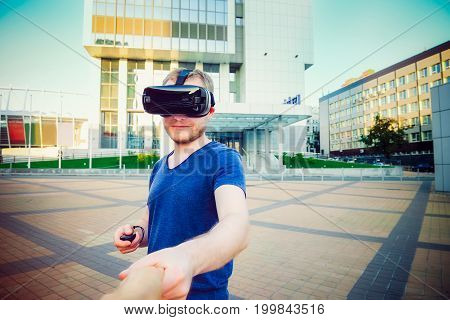 Young Man Enjoying Virtual Reality Glasses Holding Hand Of Girlfriend On The Modern City Background.