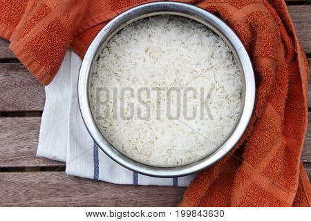 Overhead view of vessel with cooked white Basmati rice on wooden background