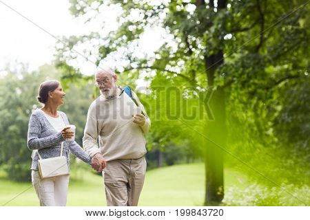 Hiking senior couple moving along country road on summer day