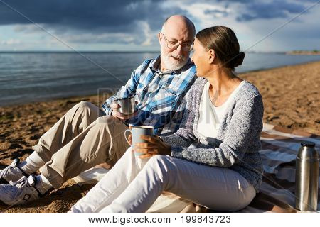 Affectionate senior couple having tea while relaxing on beach by water