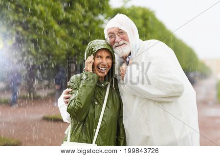 Amorous seniors in raincoats laughing in the rain while enjoying vacation